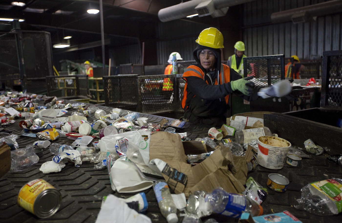 Recycling plant workers sort a stream of bottles, cardboard, and other waste.