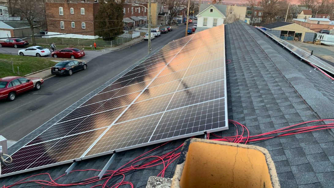 a rooftop view of shiny blue solar panels plus orange cables