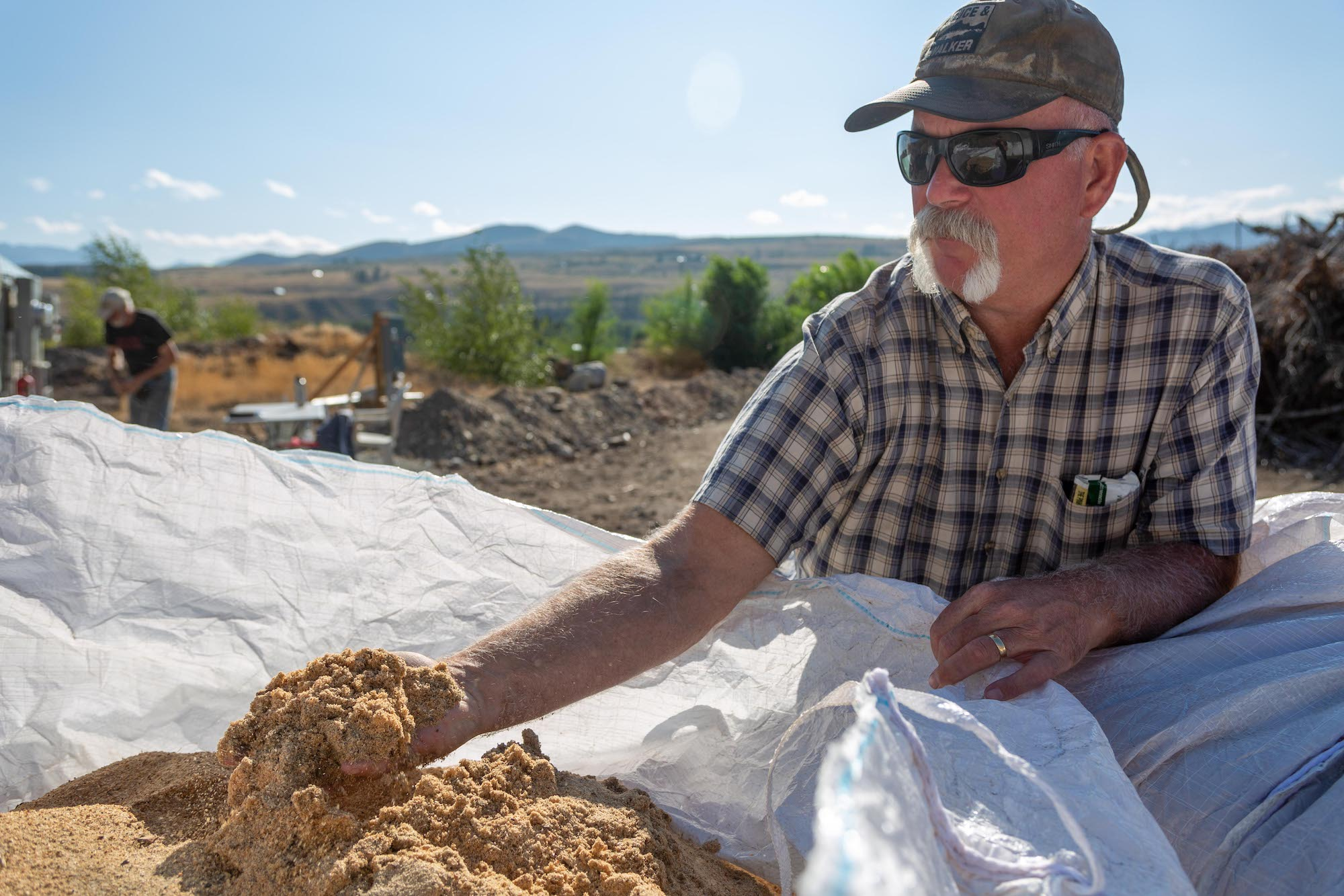 An older man wearing a plaid shoe-sleeved plaid shirt, sunglasses and a cap holds sawmill dust in his left hand. Behind him, a blue sky and a young forest let you see a mountain range rising in the horizon.