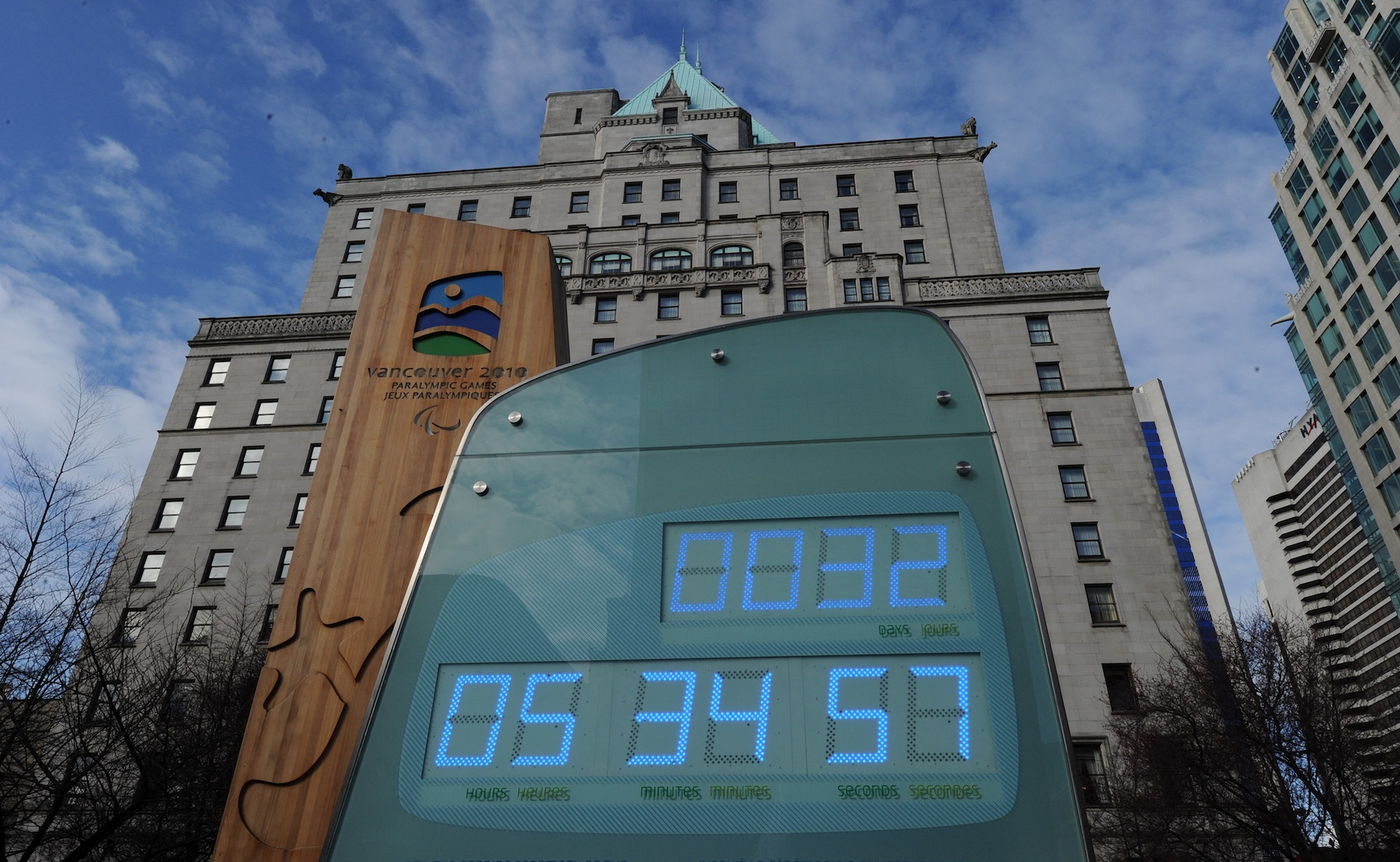 a large green sign with a countdown clock in days, hours, and minutes on a city street