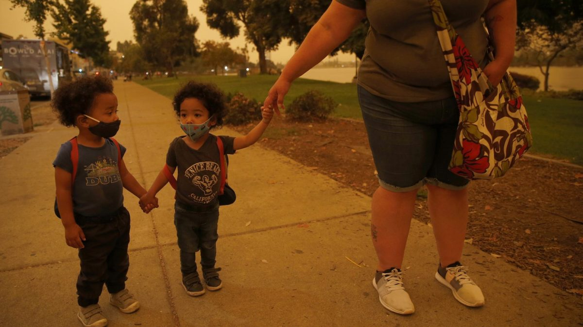 Emory and Henry Peters, 2, walk with their nanny Cynthia Chavez at Lake Merritt in Oakland, Calif., on Wednesday, Sept. 9, 2020. The unusual orange and red-hued skies were a result of smoke from the Northern California wildfires.