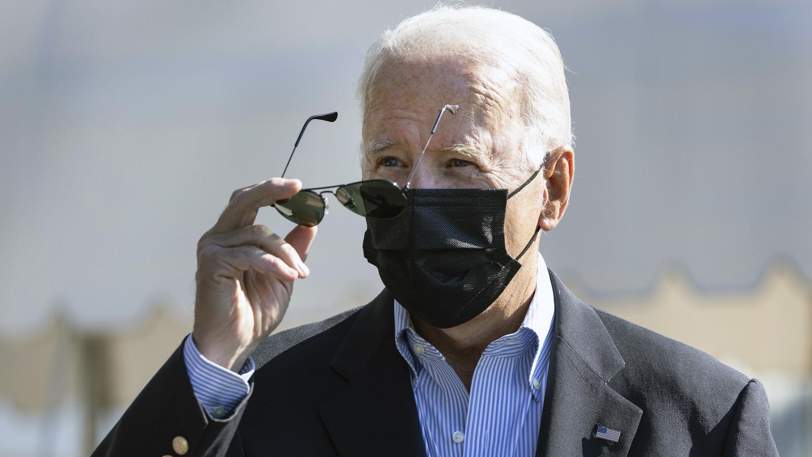 Joe Biden puts on his sunglasses under the blazing sun