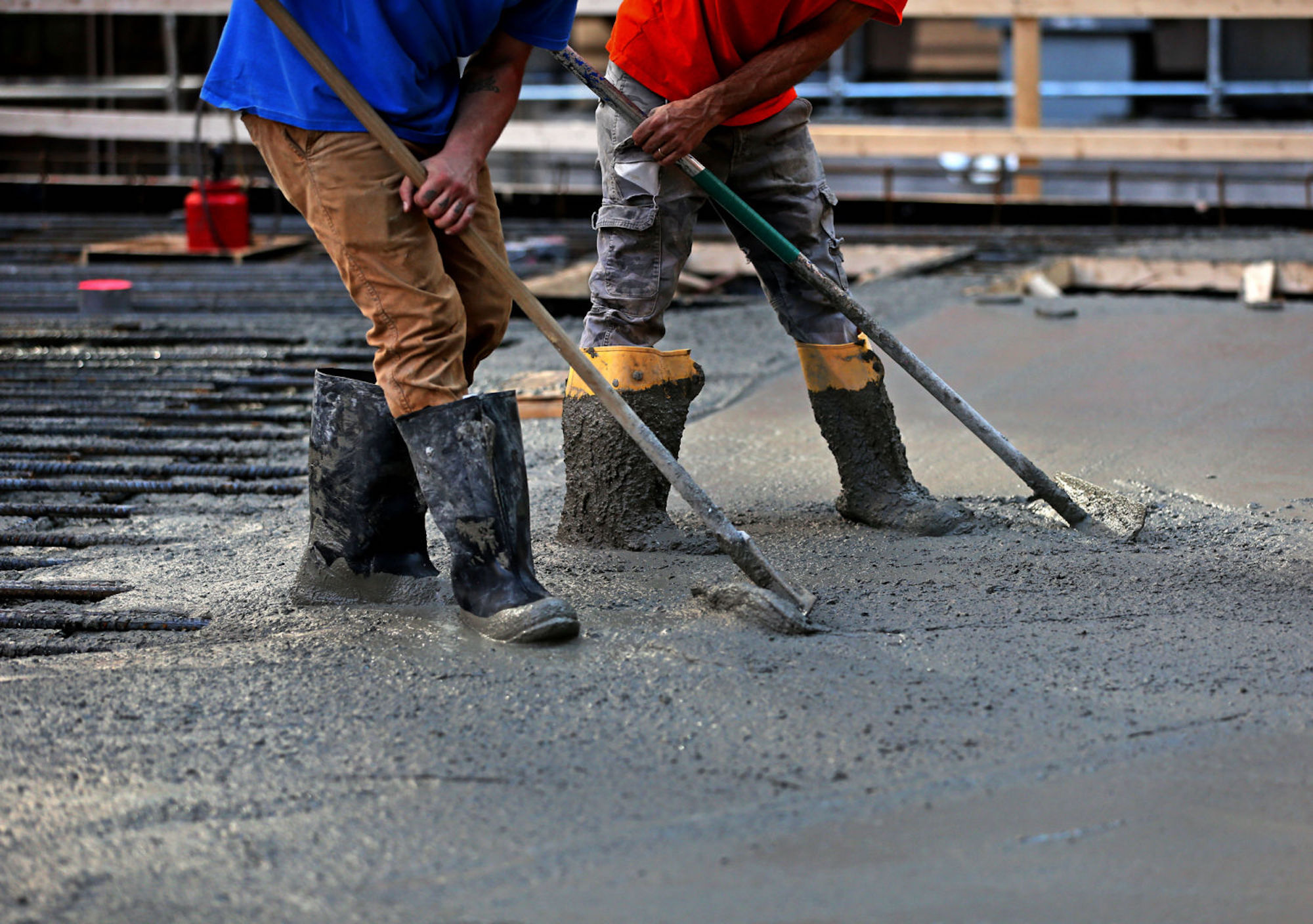Two men, one wearing a red shirt with grey pants, and the other one a blue shirt and brown plants, use shovels to distribute fresh concrete over a street. They're also wearing construction boots.