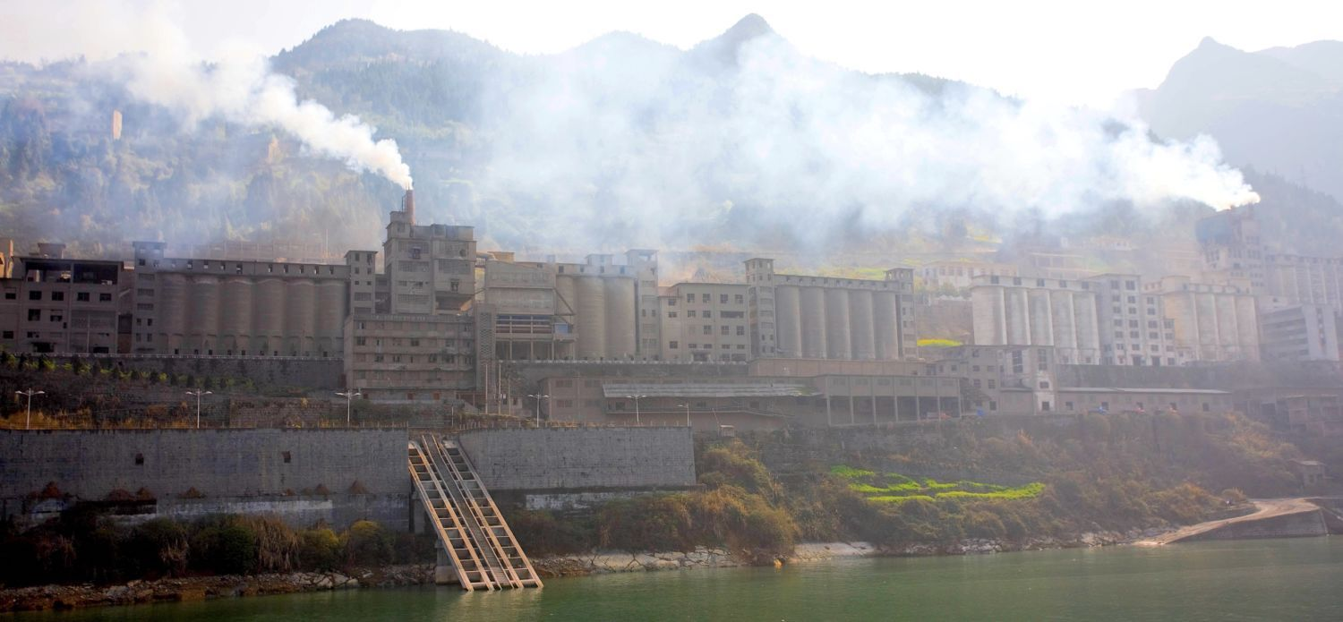 A grey, almost castle-like -looking structure emits smog. Bhind,a mountain range emerges like a wall. In front of it, near to the lens, a green, calm river passes by. A few small trees, with red and green foliage, indicate that the photo was taken during the fall months.