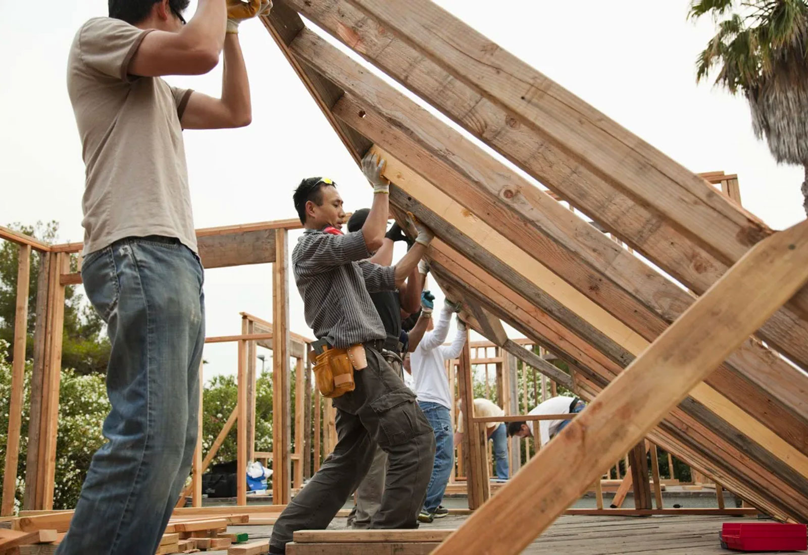 Construction workers lifting house frame