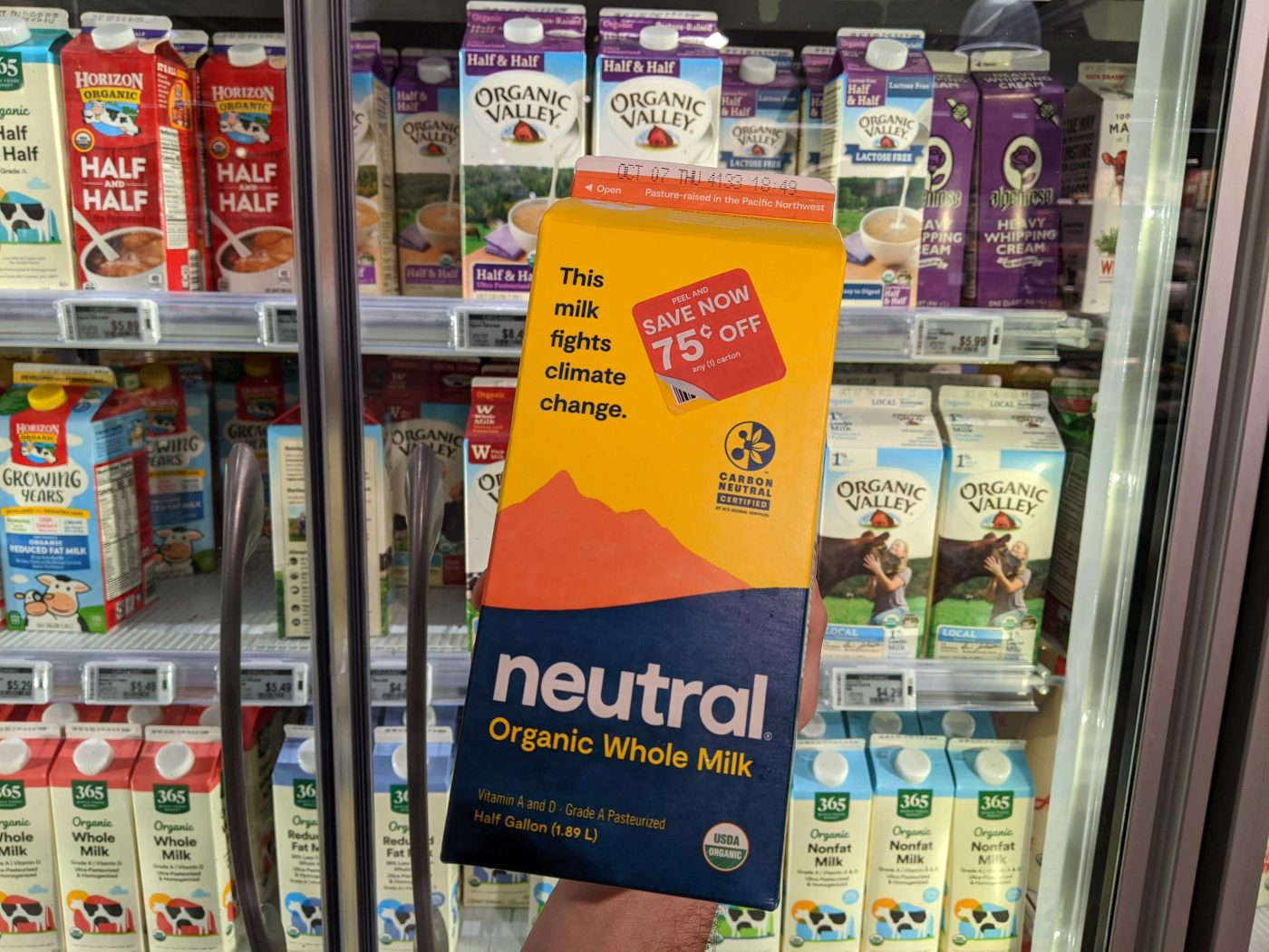 A carton of Neutral milk in front of a grocery store fridge of milk.