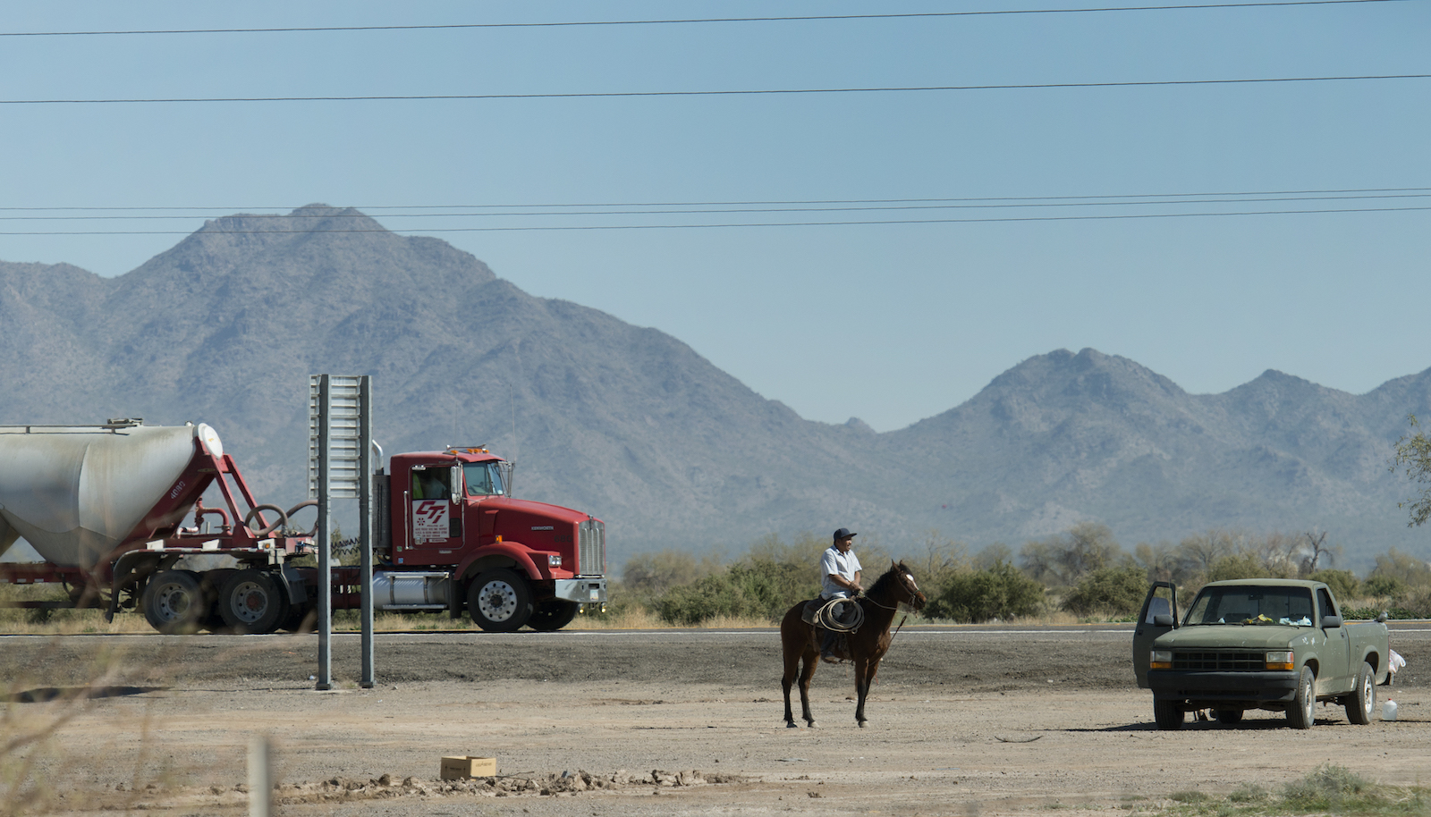 a red truck, a man on a horse, and a pickup truck stand on a dry, mountainous landscape
