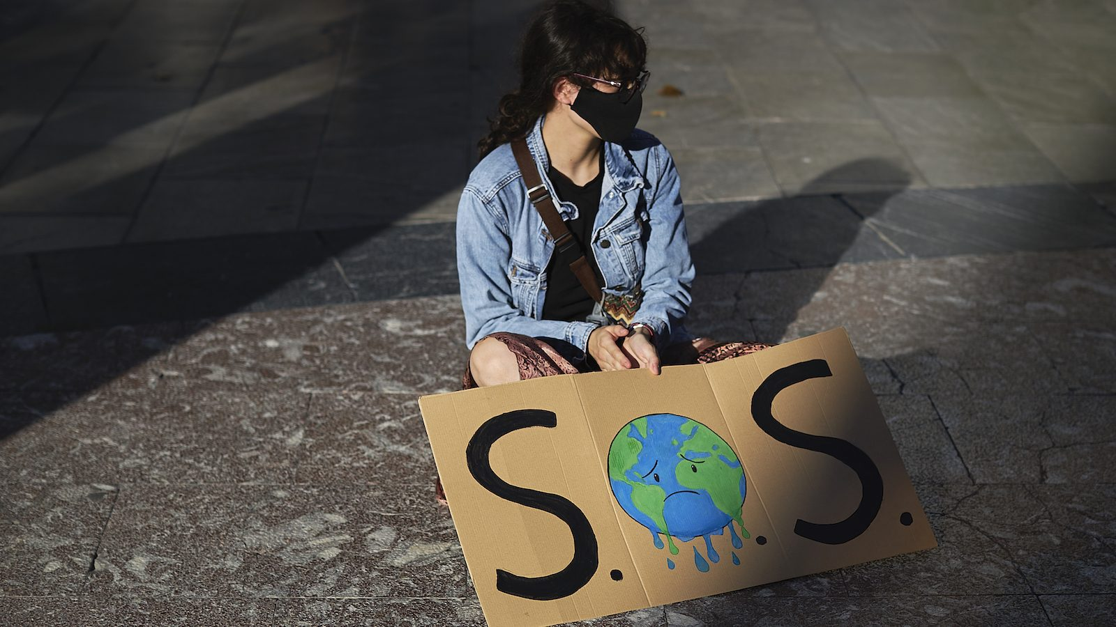 A girl sits on the ground alone with a sign saying SOS and a sad-looking Earth.