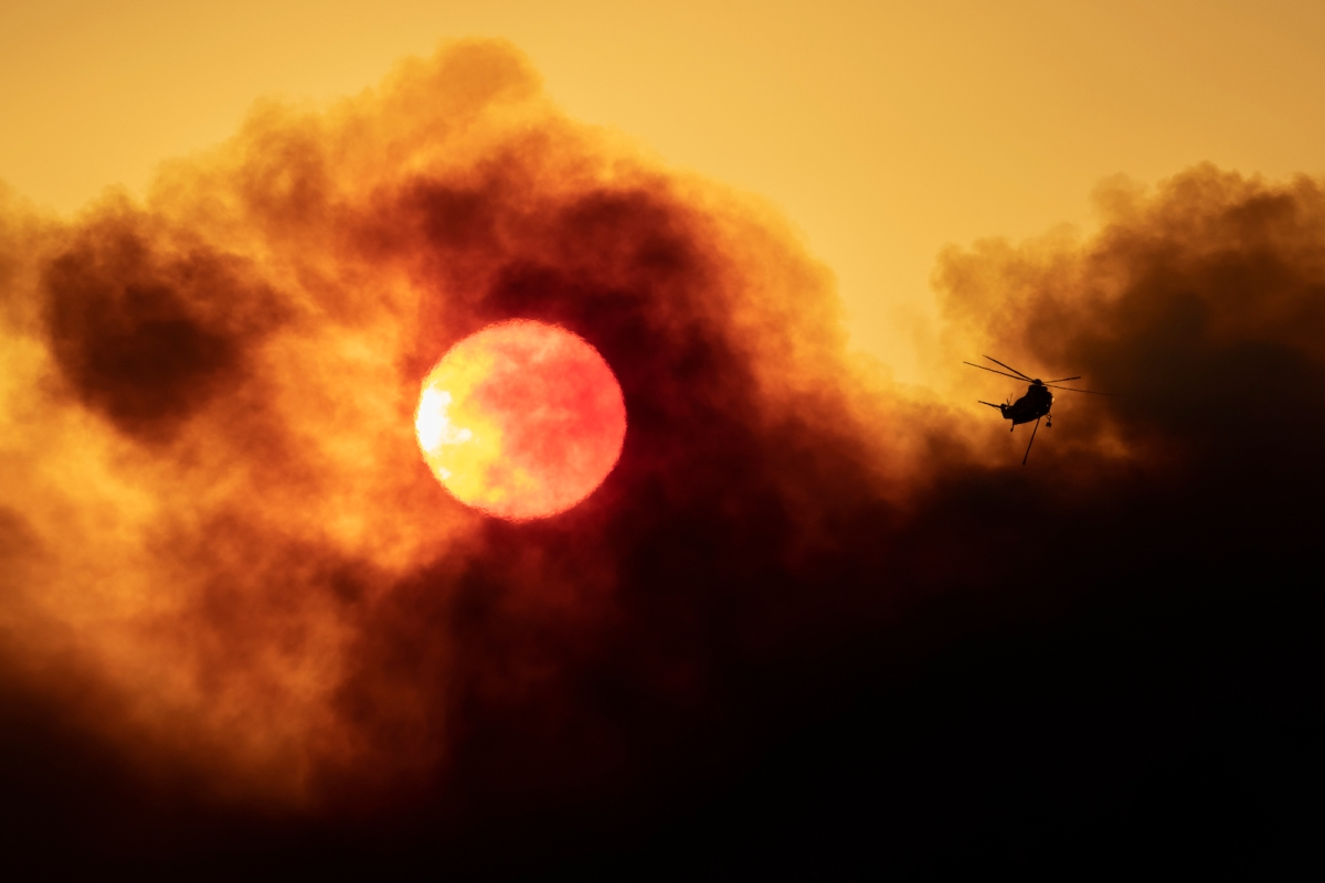 A firefighting helicopter flies as smoke from the Alisal Fire shrouds the sun on October 13, 2021 near Goleta, California. Pushed by high winds, the Alisal Fire grew to 6,000 acres overnight, shutting down the much-traveled 101 Freeway along the Pacific Coast.