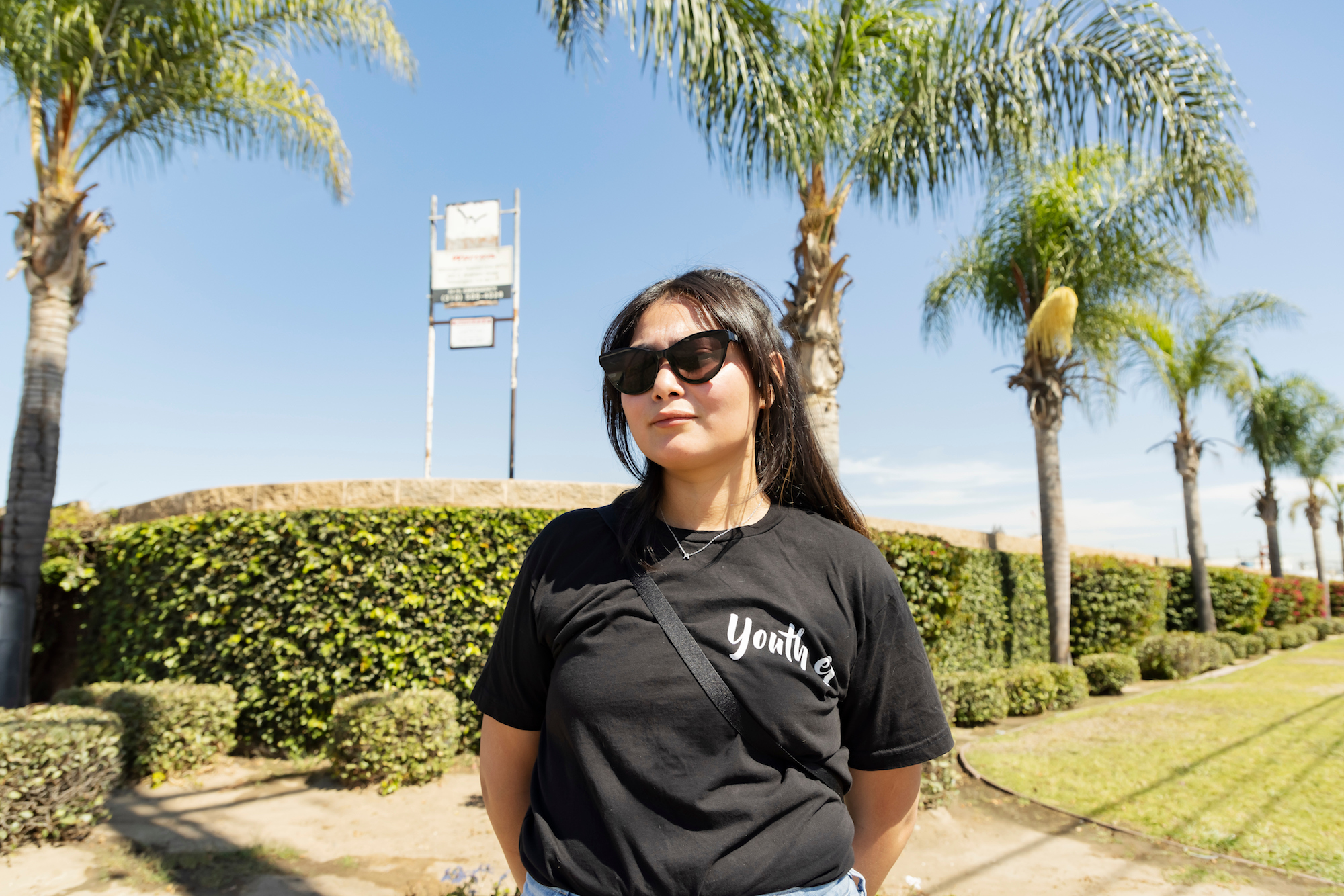 a woman with long black hair and sunglasses stands in front of a sunny street with oil infrastructure in the background