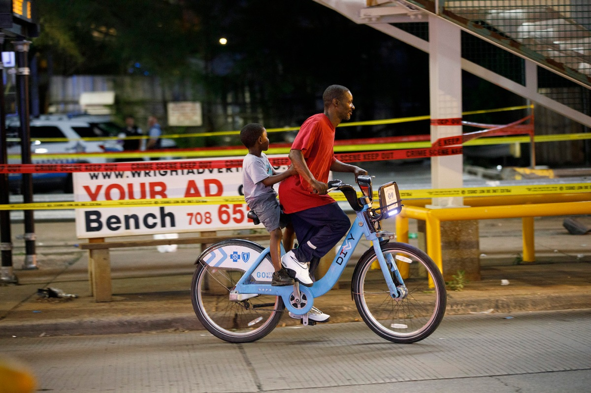 A man and child ride on a bike in Chicago.