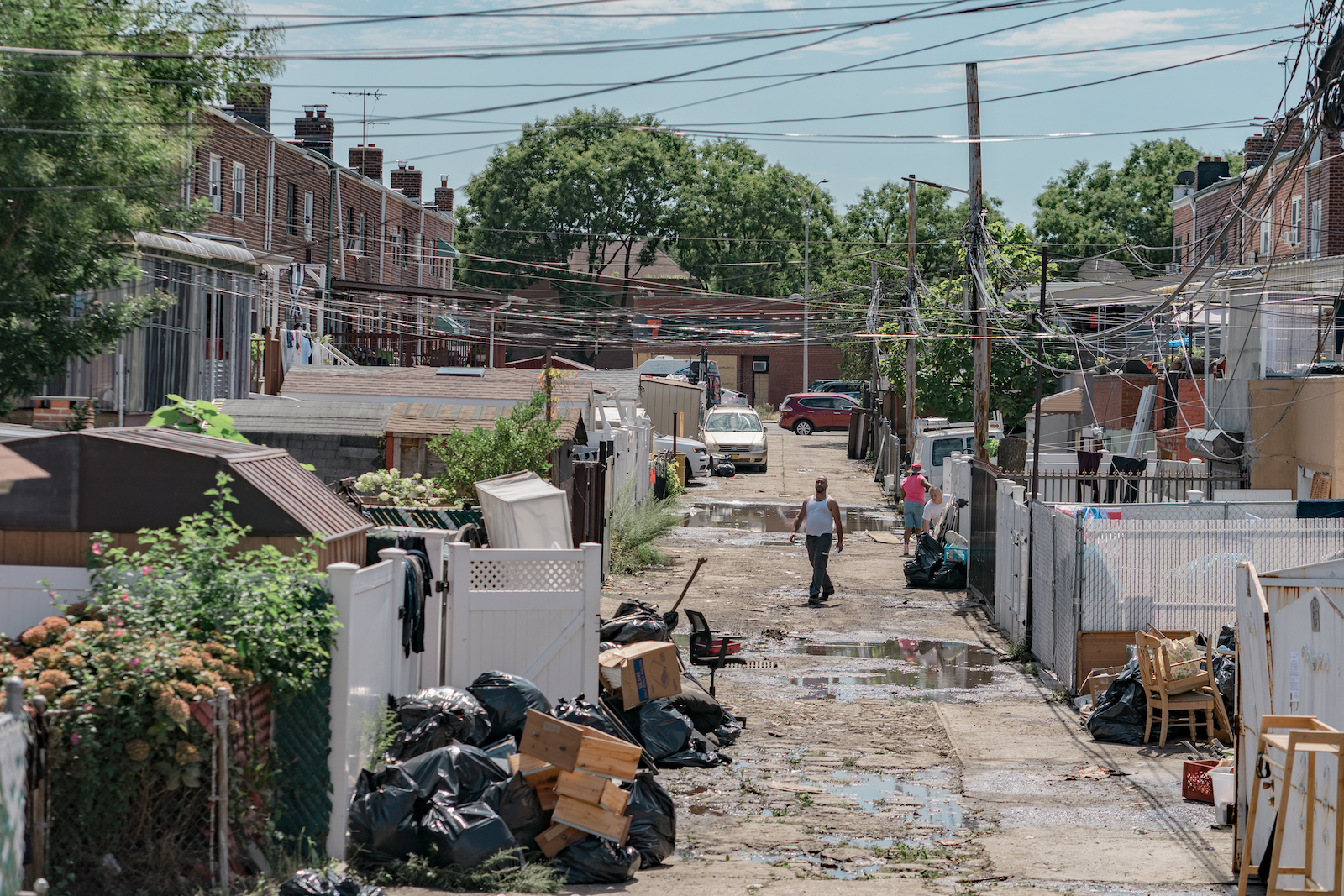 A street in New York looks wet, garbage and debris acoomultes in the sidewalk. A man wearing a white tank top and jeans walks through it.
