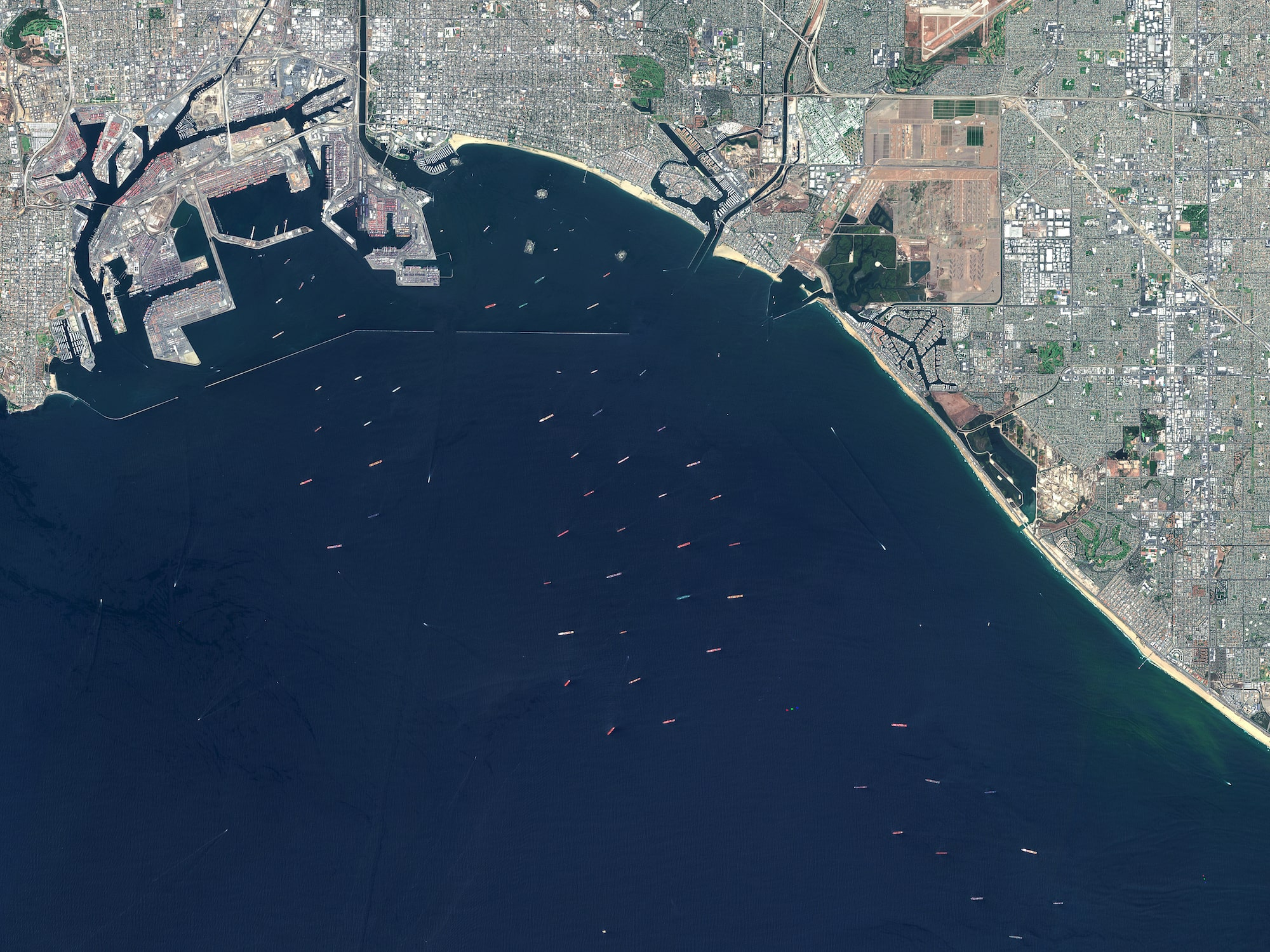 a satellite view of the port of Los Angeles with many cargo ships out at sea