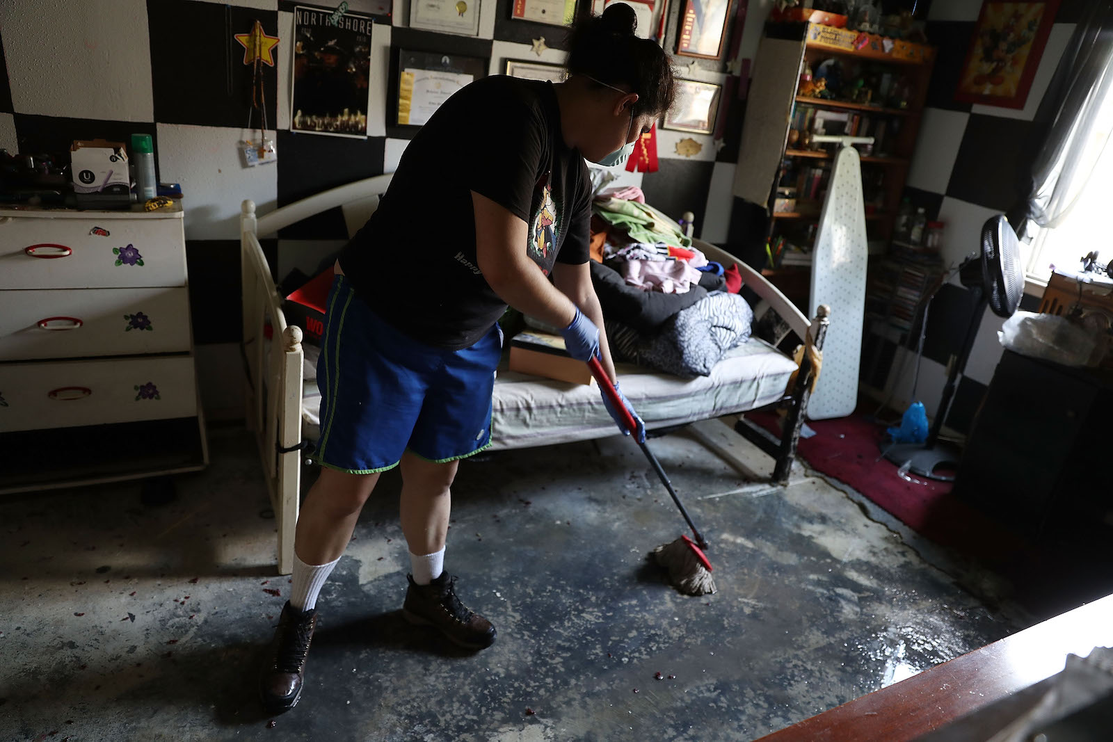 A woman with dark hair, wearing blue short and a black t-shirt, mops up floodwater in her bedroom in Houston, Texas following Hurricane Harvey in September 2017.