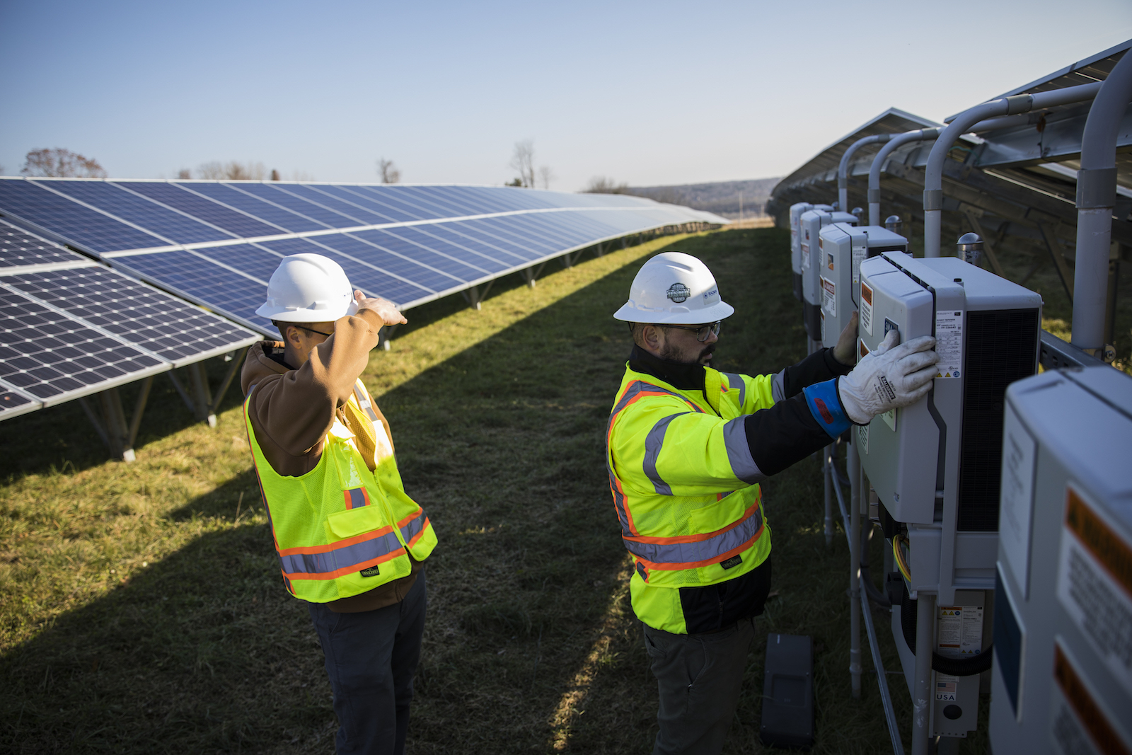 Employees from a Radian Generation's operations and maintenance team change out a faulty solar inverter along a row of solar panels December 4, 2017 in Oxford, Massachusetts. The 16.5 megawatt solar array, on what was once the largest pig farm in the northeast, is owned and operated by BlueWave Solar which feeds the generated electricity to homes and small businesses and to the Fay School and Phillips Academy Andover private schools.