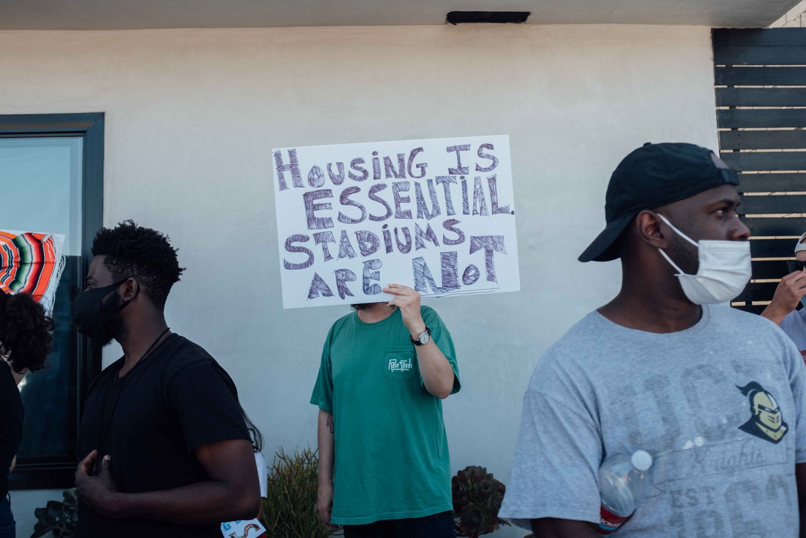 a person in a green t-shirt holds a sign that says housing is essntial stadiums are not
