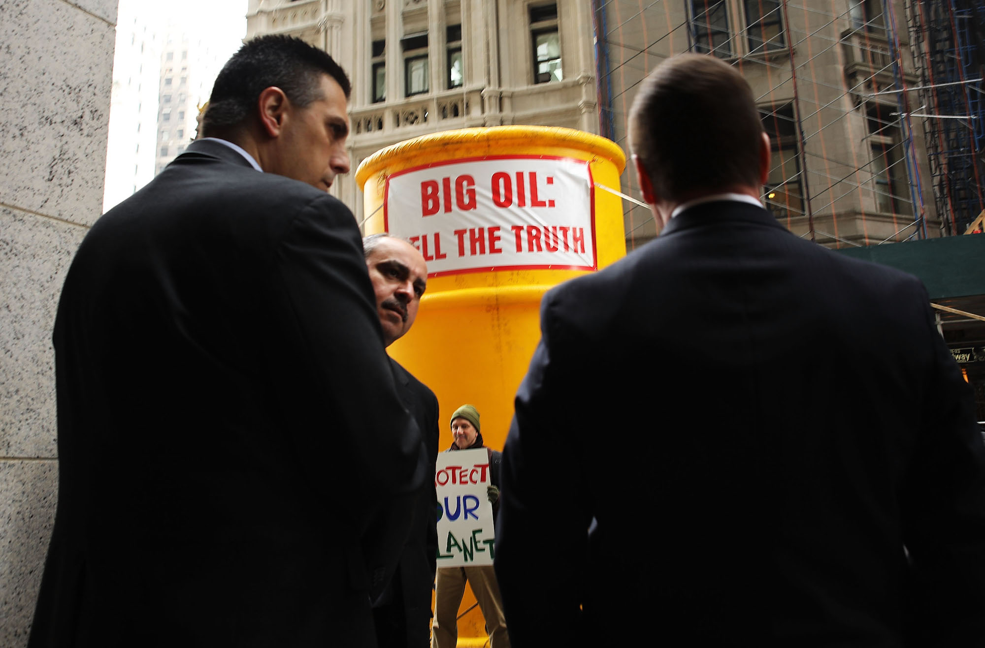 A canary-yellow blow-up stands in front of New York State Attorney General's office. Protestors rally around it, while two security guards watch the scene.