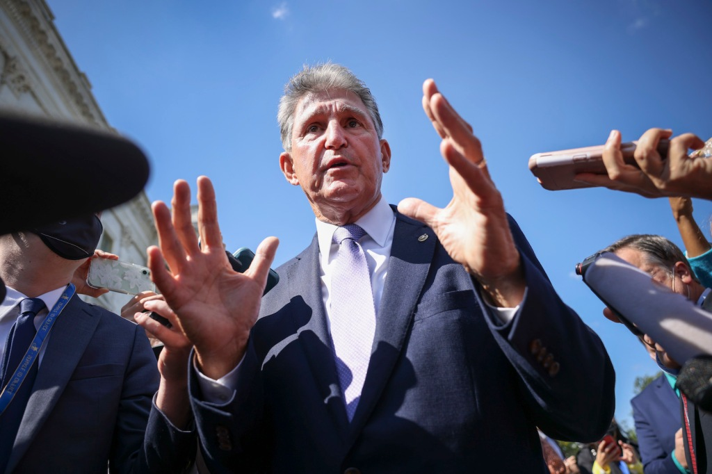 joe manchin holds up his hands as he speaks to a crowd of reporters