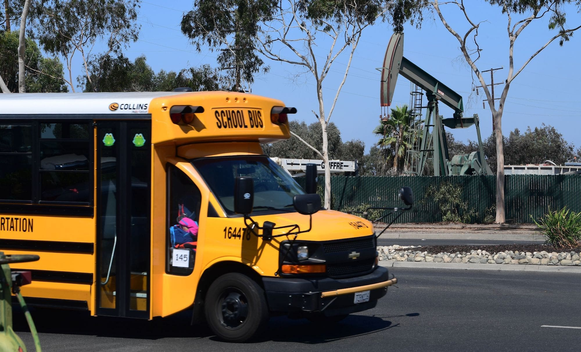 a yellow school bus parked on a street with an oil derrick visible nearby